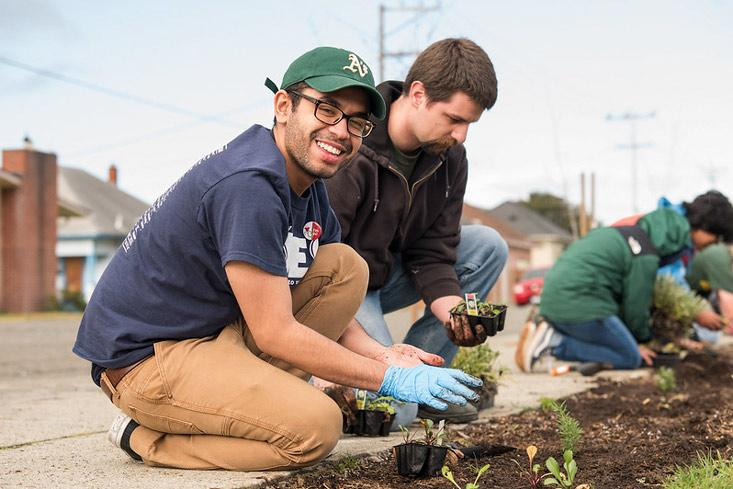 Two students planting and one smiling for the camera